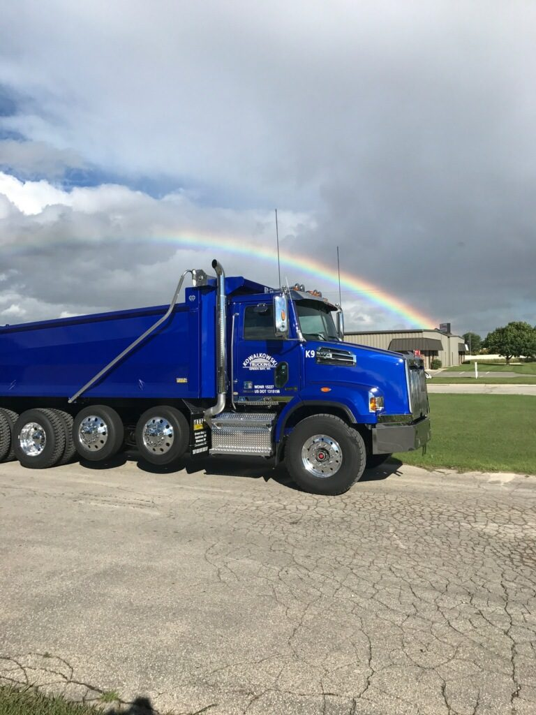 One Red-D-Mix Concrete dump truck in front of a rainbow